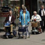 Nederland, Rotterdam, 4 mei 2006  invalide mensen ouderen senioren bejaarden  Hoogstraat R'dam / lichamelijk gehandicapten  scootmobiel mensen invalidewagen vervoer activiteiten Mobiliteit scootmobielen Verkeer  Voetganger   toegankelijkheid rolstoel gehandicapten invaliden loopwagen lopen  rijden  / winkelen voetgangersgebied voetgangers stadsgezicht straatbeeld scootmobiel bejaarden rollator, ouderen, senioren, bejaarden, Mobiliteit, vervoer, vrijheid foto: Peter Hilz